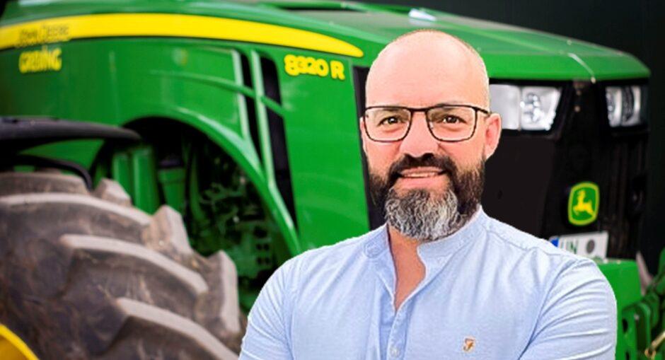Mitarbeiter Björn Cronsfoth steht vor einem grünen Traktor